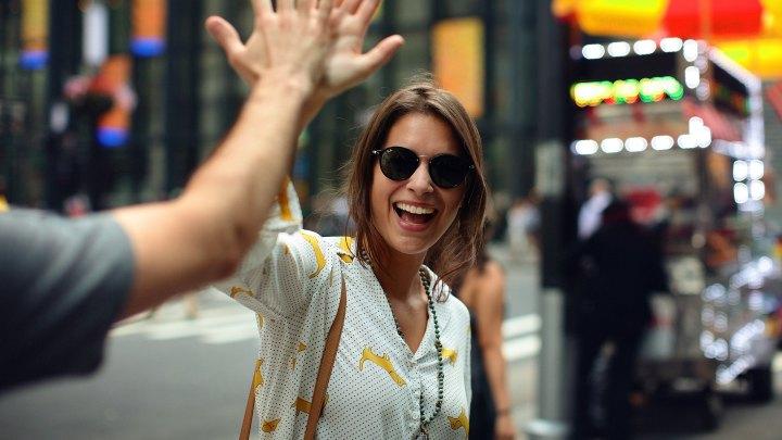 Kvinna med solgrasögon som ger en annan person en high five